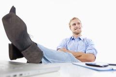 Hombre en la oficina con los pies en el escritorio fotos de archivo
