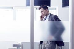 Hombre en la oficina que invita al móvil Imagen de archivo