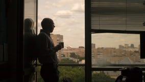 Hombre en la oficina que se coloca en la ventana y la bebida imagenes de archivo
