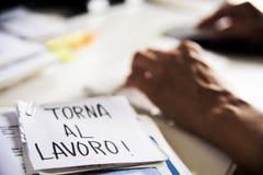 Hombre en la oficina y texto de nuevo a trabajo en italiano imagenes de archivo