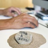 Hombre en la oficina y texto de nuevo a trabajo en italiano foto de archivo