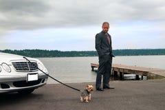 Hombre en la orilla del lago con su perro imagenes de archivo