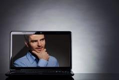 Hombre en la pantalla de una computadora portátil Fotografía de archivo