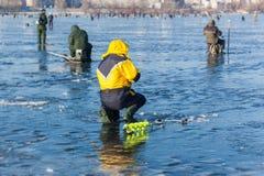 Hombre en la pesca del invierno, gente en el hielo del lago congelado, fis Imágenes de archivo libres de regalías