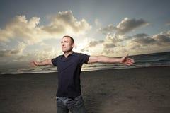 Hombre en la playa con los brazos ampliados Imagenes de archivo