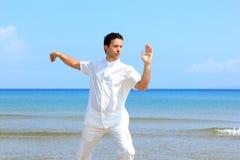 Hombre en la playa meditating Imagen de archivo libre de regalías