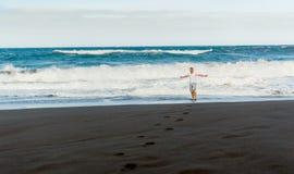 Hombre en la playa negra de la arena Foto de archivo libre de regalías