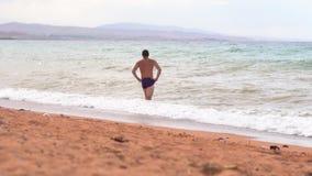 Hombre en la playa por el mar almacen de video
