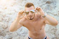 Hombre en la playa que mira a través de las gafas de sol Foto de archivo libre de regalías