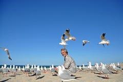 Hombre en la playa sorprendida por la multitud de gaviotas Imagen de archivo