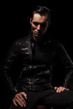 Hombre en la presentación negra de la chaqueta de cuero asentado en estudio oscuro Foto de archivo
