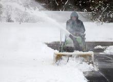 Hombre en la quitanieves del montar a caballo con nieve que sopla Imagen de archivo