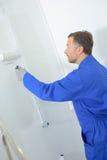 Hombre en la ropa de funcionamiento que pinta las paredes en sitio foto de archivo libre de regalías