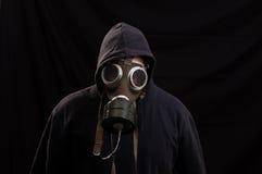 Hombre en la ropa negra que lleva una careta antigás clásica sobre una parte posterior de la oscuridad Fotos de archivo libres de regalías