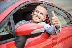 Hombre en la rueda de su nuevo coche Foto de archivo