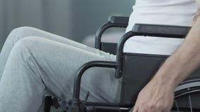 Hombre en la silla de ruedas que da vuelta de nuevo a la cámara, amargura inconsolable de la condición metrajes