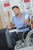 Hombre en la silla de ruedas que hace gesto indiferente Imagen de archivo