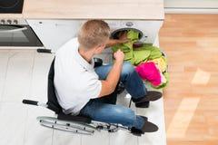 Hombre en la silla de ruedas que pone el lavadero en la lavadora Imagen de archivo libre de regalías