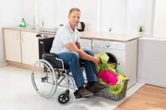 Hombre en la silla de ruedas que pone la ropa en la lavadora Foto de archivo libre de regalías