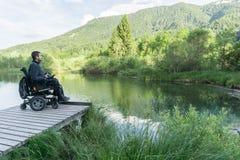 Hombre en la silla de ruedas que sostiene la cámara mirrorless cerca del lago en naturaleza foto de archivo