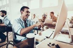 Hombre en la silla de ruedas que trabaja en el ordenador en oficina imagen de archivo