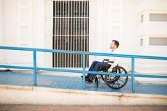 Hombre en la silla de ruedas que va para arriba una rampa fotografía de archivo libre de regalías