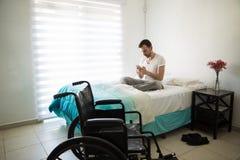 Hombre en la silla de ruedas usando su teléfono Fotos de archivo libres de regalías