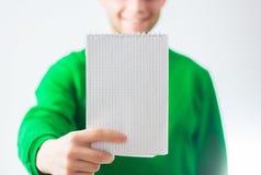Hombre en la sonrisa de la camiseta del verdor, mano que lleva a cabo la nota espiral en blanco Imagenes de archivo