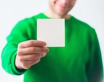 Hombre en la sonrisa de la camiseta del verdor, mano que sostiene A4 el aviador en blanco, D Imágenes de archivo libres de regalías