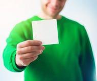 Hombre en la sonrisa de la camiseta del verdor, mano que sostiene A4 el aviador en blanco, D Imagenes de archivo