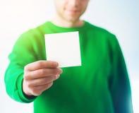 Hombre en la sonrisa de la camiseta del verdor, mano que sostiene A4 el aviador en blanco, D Fotos de archivo libres de regalías