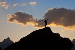 Hombre en la tapa de un acantilado en la puesta del sol Fotografía de archivo libre de regalías