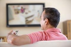 Hombre en la televisión de observación de la sala de estar Foto de archivo libre de regalías