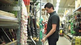 Hombre en la tienda que examina la pala de la nieve Cliente que se prepara para el invierno almacen de metraje de vídeo