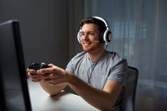 Hombre en las auriculares que juegan al videojuego del ordenador en casa Imagen de archivo libre de regalías