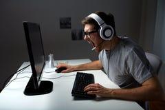 Hombre en las auriculares que juegan al videojuego del ordenador en casa Foto de archivo