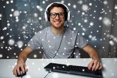 Hombre en las auriculares que juegan al videojuego del ordenador en casa Imágenes de archivo libres de regalías