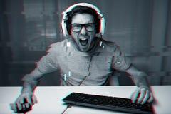 Hombre en las auriculares que juegan al videojuego del ordenador en casa Fotografía de archivo
