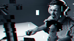 Hombre en las auriculares que juegan al videojuego del ordenador en casa Fotos de archivo libres de regalías