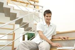 Hombre en las escaleras con la computadora portátil Imagen de archivo
