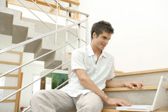 Hombre en las escaleras con la sonrisa de la computadora portátil Fotografía de archivo libre de regalías