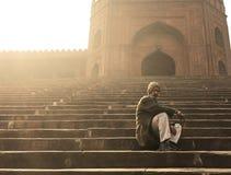 Hombre en las escaleras fuera de Jama Masjid, Delhi vieja, la India Foto de archivo