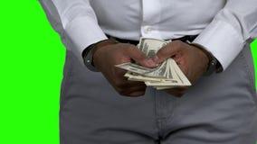 Hombre en las esposas que sostienen billetes de banco del d?lar almacen de metraje de vídeo