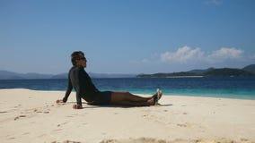 Hombre en las gafas de sol que se sientan en la playa almacen de video