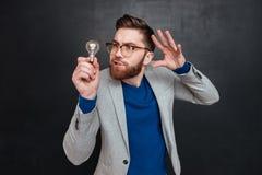 Hombre en las lentes que sostienen la bombilla y que gesticulan con la mano Imágenes de archivo libres de regalías
