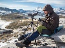 Hombre en las montañas con los prismáticos y el telescopio Imagen de archivo