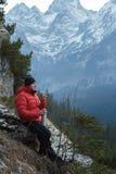 Hombre en las montañas del invierno que descansan y que beben de la taza del metal del frasco de vacío Fotos de archivo