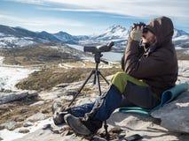 Hombre en las montañas que miran a través de los prismáticos debajo del cielo azul Fotos de archivo libres de regalías