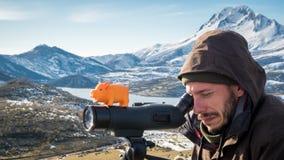 Hombre en las montañas que miran a través del telescopio con su guarro a Fotos de archivo