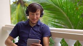 Hombre en las zonas tropicales que habla con los amigos y la familia en la llamada video usando una tableta y los auriculares de  almacen de metraje de vídeo
